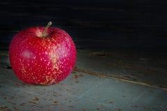 Einzelner roter Apfel auf einer rustikalen Tabelle Lizenzfreie Stockfotos