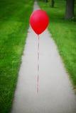 Einzelner roter Ballon Stockbild