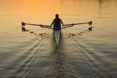Einzelner Rower am Sonnenaufgang Stockfotos