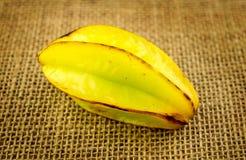 Einzelner starfruit Carambola gegen Hintergrund des Leinwandgroben sackzeugs Lizenzfreie Stockbilder