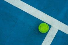 Einzelner Tennisball auf blauem Tennisplatz Stockfoto