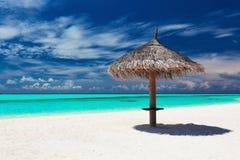 Einzelner tropischer Strandschirm auf romantischem weißem Strand Lizenzfreies Stockbild
