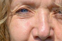 Einzelnes blaues Auge und Nase einer Frau von mittlerem Alter stockfotografie