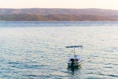 Einzelnes Boot im Meer, sichtbare Berge und Insel fahren die Küste entlang. Lizenzfreie Stockbilder