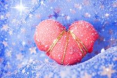 Einzelnes eingeschneites rotes Herz Stockfotos