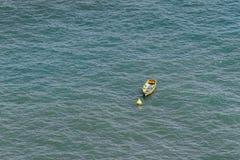 Einzelnes gelbes Boot im Meer Stockfotos