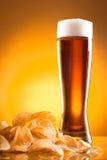 Einzelnes Glas Bier und Kartoffelchips Stockfotos