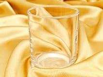 Einzelnes Glas am goldenen Hintergrund Stockfotografie