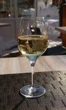 Einzelnes Glas weißer Wein auf der Tabelle. Lizenzfreies Stockbild