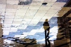 Einzelnes Mannreflexionsschattenbild auf nassem Bürgersteig stockbilder