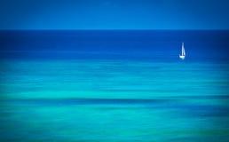 Einzelnes Segelboot auf blauem Ozean Stockfotografie