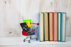 Einzelteile für Schule in einer den Einkaufslaufkatze und -büchern Stockfoto