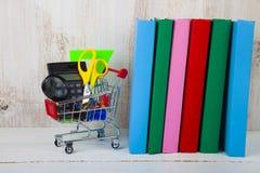 Einzelteile für Schule in einer den Einkaufslaufkatze und -büchern Lizenzfreie Stockfotos