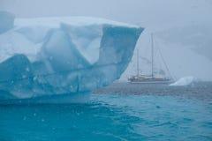 Einzigartiger gezackter blauer gestreifter Eisberg der Antarktis mit Segelboot lizenzfreie stockfotografie