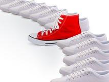 Einzigartiger roter Gummischuh in Folge von Schuhen Lizenzfreies Stockfoto