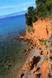 Einzigartiger roter Sandstein schaukelt über kleinen steinigen Strand auf norhern Seite von Vir-Insel, Kroatien, adriatische Regi Stockbild