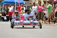 Einzigartiges Auto Vater-And Daughter Steers im Seifenkistenrennen Stockfoto