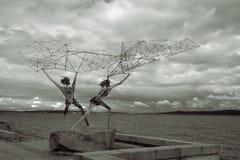 Einzigartiges Skulptur ` Fischer ` mit geometrischer Zahl eines Metallfischennetzes Stockbilder