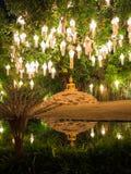 Einziger goldener Buddha, der im Lotussitz unter einem großen Baum sitzt Stockbilder