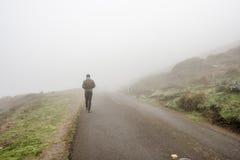Einziger Mann, der durch den weißen Nebel geht Stockbild