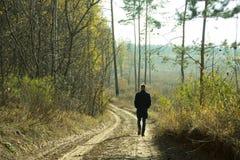 Einziger Mann, der entlang eine leere Straße im Wald geht Lizenzfreies Stockbild