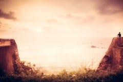 Einziger Reisendmann auf der Klippe, die mit Inspiration auf Horizont mit Sonnenlicht während des Sonnenuntergangs mit Effekt des stockbild