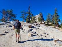 Einziger Wanderer mit Pole-Aufstiegs-Granit-Abhang lizenzfreies stockbild