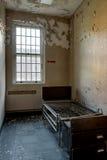 Einziges Bett innerhalb des trostlosen geduldigen Raumes - verlassenes Krankenhaus stockfotos