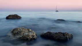 Einziges Boot auf dem Horizont Stockbilder