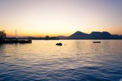 Einziges jetski auf einem See bei Sonnenuntergang mit Hügeln im Abstand Stockfotografie