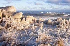 Eis auf dem Gras und den Steinen Stockbild