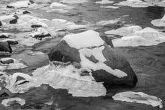 Eis auf gefrorenen Felsen im Fluss Stockfotografie