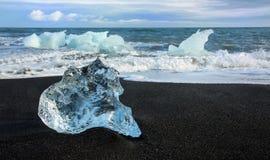 Eis auf schwarzem Sand Stockbilder