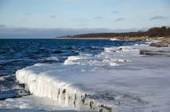 Eis bedeckte flache Felsenküste Stockfoto