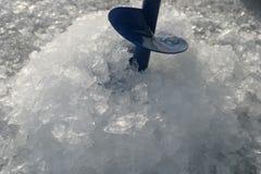 Eis bohrt herein das Loch Stockfoto