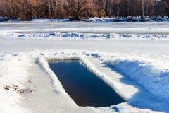 Eis-Loch in gefrorenem See Stockbilder