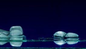 Eis-Würfel, der eine Glasoberfläche schmilzt und weitergeht stock video footage