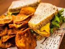 Eisandwich und selbst gemachte Chips stockfotos