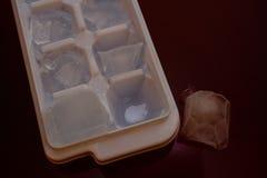 Eisbehälter und ein Eisblock Stockfoto