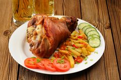 Eisbein with french fries, vegetables and beer Royalty Free Stock Photo