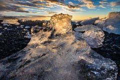 Eisberg auf schwarzem Sandstrand von Island bei Sonnenaufgang Stockbilder