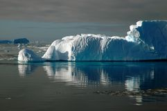 Eisberg im Sonnenlicht mit Wasserreflexion stockfoto
