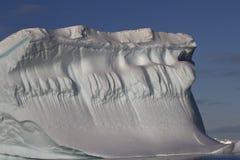 Eisberg mit einer verbreiteten Wand gegen den blauen Himmel Lizenzfreies Stockbild
