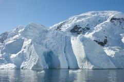 Eisberg mit Höhle und Berg hinter ihm Lizenzfreies Stockbild
