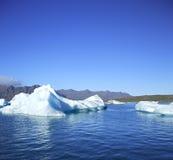 Eisberge gegen die Berge lizenzfreie stockbilder