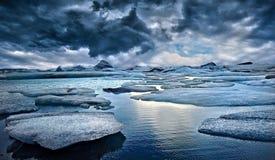 Eisberge gegen stürmischen Himmel lizenzfreie stockbilder