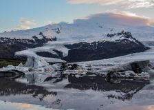 Eisberglagune Fjallsarlon mit sich hin- und herbewegenden Eisbergen und drastische Himmelreflexion im Wasser, Nationalpark Vatnaj stockbild