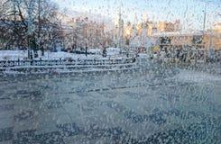 Eisblumen auf einem Glas Stadtansicht durch ein bereiftes Fenster Konzept von extrem Zuständen des kühlen Wetters lizenzfreie stockfotos