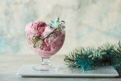 Eiscreme gedient in einer Glasschüssel Angezeigt mit Zuckerstangen auf hölzerner rustikaler Tabelle Funkelnder Christbaumkerzehin Stockfotografie