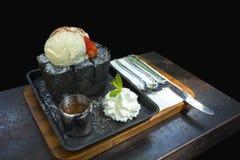 Eiscreme mit Holzkohlenbrot und Honigsaft auf der braunen Platte Stockbild